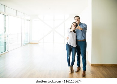 Full length of mid adult couple feeling happy about buying a new house