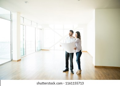 Full length of mid adult owners examining blueprints of their new house