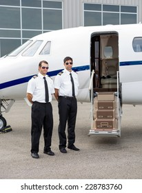 Full length of mid adult pilots standing by private jet with open door