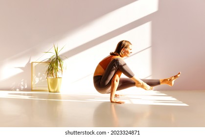 Full length of middle-aged sportive active woman in sportswear standing in yoga asana, doing balance exercise in light sunny studio, mature female practicing sport. Age, wellness and health