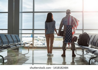 Full length of military man with American flag on shoulders looking through the window with his wife in waiting room. He just came back from army. Homecoming and military concept