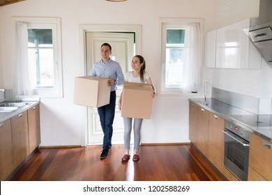 Full length millennial wife and husband hold carton boxes with belongings standing in modern kitchen at home. Attractive happy couple bought new house. Moving relocate day mortgage and tenant concept