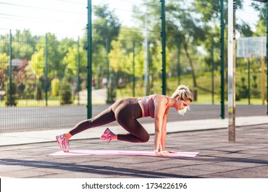 Full length, motivated athletic woman in tight pants training on mat outdoor summer day, doing plank crunch abs exercise, alternating knee, aerobics pilates workout. Health care, sports activity