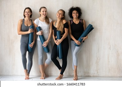 Full length of multi-ethnic vivacious women smiling looking at camera holding carpets leaned on wall background, comfy tops and pants sportswear advertisement, sport club instructors portrait concept