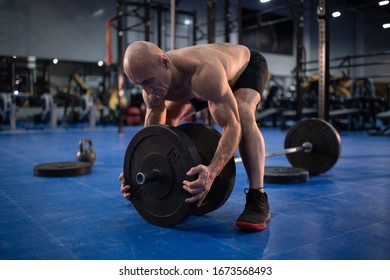 Full length muscular bald senior man squatting and placing heavy weight plates on barbell during weightlifting workout in gym