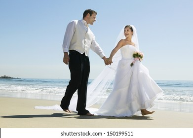 Full length of newlywed couple holding hands while walking on beach