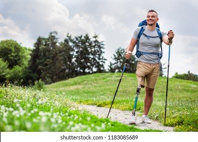 Full length of a nice positive young man with prosthesis having a walk outdoors and enjoying his hobby
