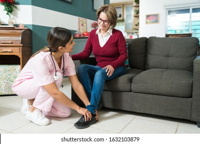 Full length of nurse helping smiling elderly woman in wearing shoe at home