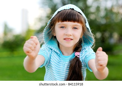 Full length outdoor portrait of adorable child girl in blue jacket with hood posing with clenched fists
