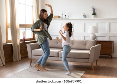 Full length overjoyed barefoot young mommy babysitter dancing to energetic music with school aged girl on floor carpet at home. Excited mother having fun with small child daughter in living room.