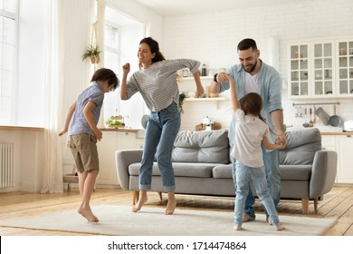 Full length overjoyed family of four jumping to music in modern studio living room. Excited young married couple dancing with playful little children siblings, spending active free time at home. - Shutterstock ID 1714474864
