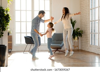Full length overjoyed family of three having fun together. Smiling young father holding hands of happy little daughter, dancing together to favorite music while joyful mother jumping singing song.