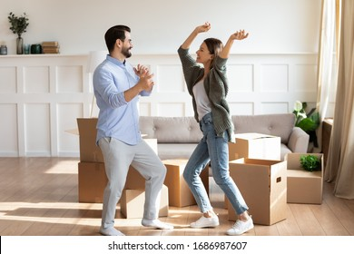 Full length overjoyed married couple dancing in living room, having fun between cardboard boxes. Happy family spouses celebrating moving day in new apartment flat house, real estate concept.