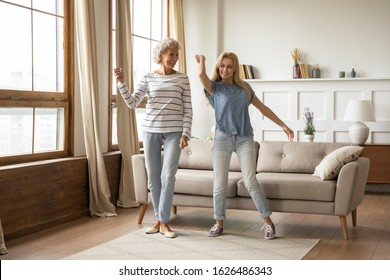 Full length overjoyed middle aged grey haired elderly woman dancing to energetic music with grown up blonde daughter. Happy smiling two generations female family having fun together in living room.