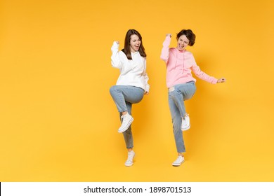 Full length of overjoyed two young women friends 20s wearing basic white pink hoodies doing winner gesture celebrating clenching fists say yes isolated on bright yellow background studio portrait