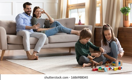 Full length overjoyed young couple resting on comfortable sofa, watching comedian movie on digital tablet, while little kids brother sister playing toys wooden blocks on floor carper in living room.