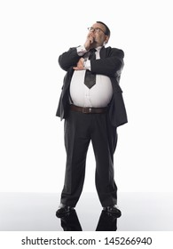 Full length of an overweight businessman standing with hand on chin against white background