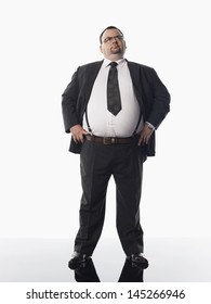 Full length of an overweight businessman standing against white background