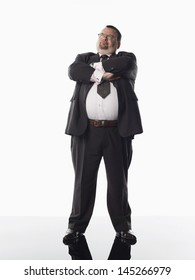 Full length of an overweight businessman standing with arms crossed against white background