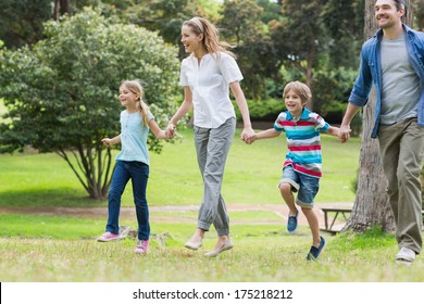 Full length of parents and kids walking in the park