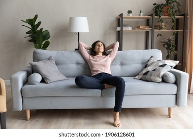 Full length peaceful happy young woman relaxing on comfortable sofa, breathing fresh air, enjoying mindful lazy moment indoors. Smiling millennial caucasian lady meditating alone in living room.