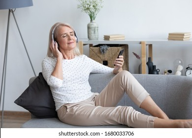 Full length peaceful mature retired lady enjoying favorite music in earphones, chilling on comfortable sofa at home. Tranquil older woman listening to classic tracks, chosen from mobile application.