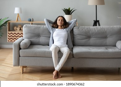 Full length peaceful woman with closed eyes resting on couch, leaning back with hands behind head, enjoying lazy weekend at home, calm young female relaxing, daydreaming, taking nap on sofa