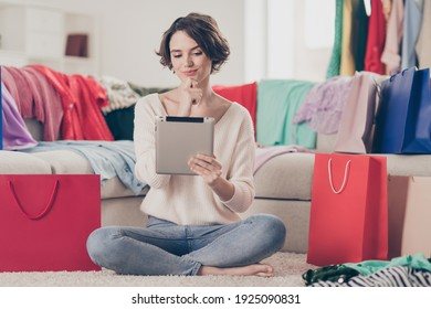 Full length phot of of thoughtful young woman look tablet choose clothes buy bags shop sit floor indoors inside house