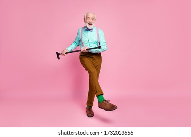 Full length photo of active grandpa moving dance pensioner party use walk stick raise leg wear mint shirt suspenders bow tie pants shoes green socks isolated pink pastel background