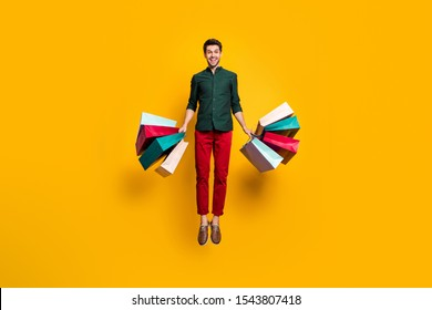 Full length photo of amazed funky crazy guy jump hear wonderful sales scream wow go shop buy purchase hold many bags wear stylish green shirt red pants trousers isolated yellow color background