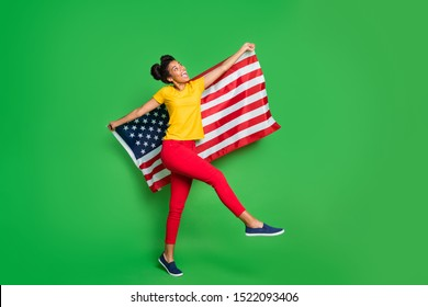 Full length photo of amazing dark skin lady celebrating independence usa day carrying national flag on parade marsh wear casual yellow t-shirt red pants isolated green background