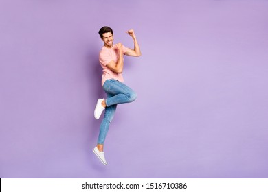 Full length photo of amazing guy jumping high at sports competitions supporting favorite team wear casual outfit isolated on purple color background