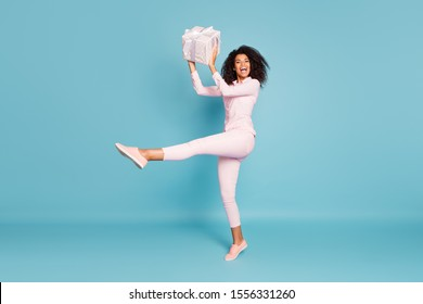 Full length photo of amazing wavy dark skin lady holding large wrapped giftbox came to  party best guest wear pink shirt pants isolated blue color background