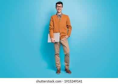 Full length photo of astonished happy man hold computer hand in pocket isolated on blue color background