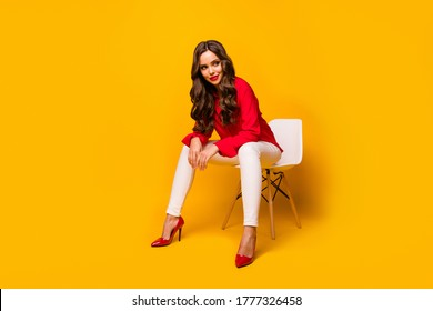 Full length photo of attractive chic business lady sit bossy comfy chair flirty mood look side empty space wear red shirt white trousers high-heels isolated yellow vivid color background
