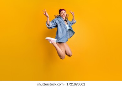 Full length photo of attractive lady long hairdo good mood students party jump high up showing v-sign symbols wear denim shirt shorts hat shoes isolated yellow color background