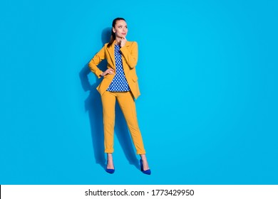 Full length photo of attractive nice worker lady look side empty space arm on chin wear yellow blazer suit trousers dotted blouse footwear high-heels isolated bright blue color background