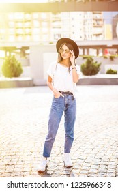 Full length photo of a beautiful girl in hat with sunglasses walkin on the street
