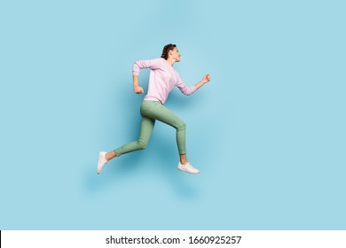 Full length photo of beautiful lady jumping high up rushing finish line running marathon champion competitive soul wear casual pink sweater green pants isolated blue color background