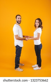 Full length photo of caucasian couple laughing and holding hands isolated over yellow background