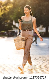 Full length photo of caucasian happy woman wearing trendy summer outfit walking through city street and holding cell phone