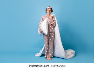 Full length photo of charming happy woman hold blanket pillow wear pajama barefoot isolated on pastel blue color background
