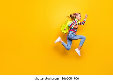 Full length photo of cheerful kid jump run speedy lesson wear striped sweater denim jeans suspenders overalls sneakers rucksack backpack isolated over bright shine yellow color background