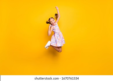 Full length photo of cheerful kid jump enjoy rejoice win lottery sales raise fists scream yeah wear checkered skirt isolated bright shine color background