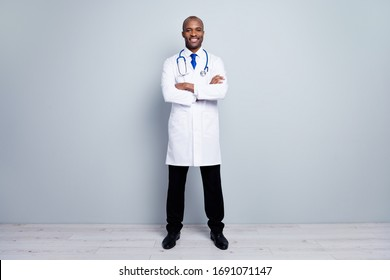 Full length photo of confident family doc dark skin guy meet patients virology clinic arms crossed friendly professional wear long lab coat tie pants shoes isolated grey color background