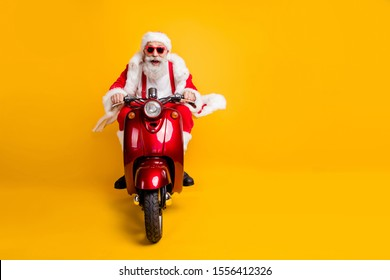 Full length photo of crazy funky santa claus in red hat drive motorcycle ride fast hurry to x-mas noel celebration wear shirt suspenders isolated over yellow color background