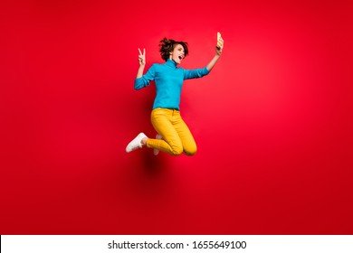 Full length photo of crazy funky bob brunette hair girl jump enjoy spring fall holiday make selfie v-sign smartphone blogging wear blue sweater yellow outfit isolated bright red color background