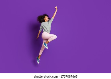 Full length photo of crazy funny afro american girl jump hold hand try catch parasol wear casual style pink outfit isolated over purple color background