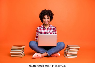 Full length photo curly beautiful lady sit floor hold hands notebook online courses wear specs casual checkered plaid shirt isolated orange background