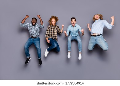 Full length photo of ecstatic guys pals hear corona virus victory news jump raise fists scream yes wear checkered plaid shirt isolated over gray color background